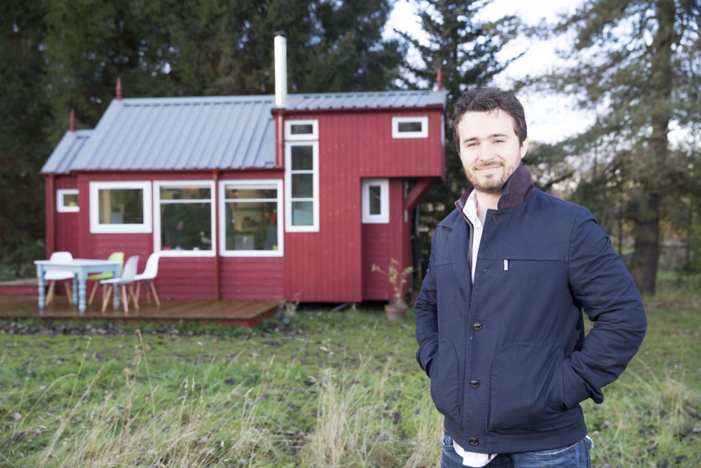 Josh Littlejohn outside red garden cabin announcing new project for Social Bite