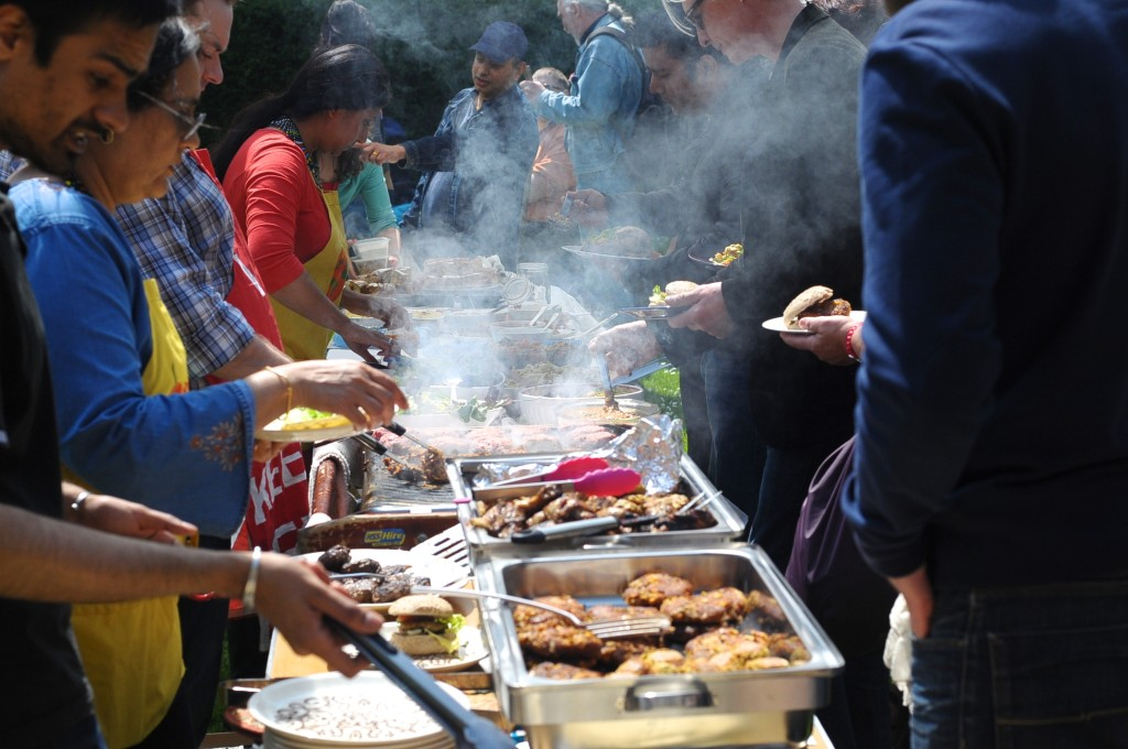 A row of cooks turning food over barbecue coals, lots of smoke and steam rising from the pans