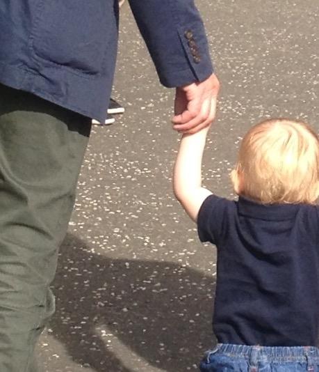 Grandad holding toddler grandson's hand