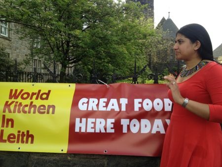 Meena in red dress standing beside red and yellow banner of World Kitchen in Leith