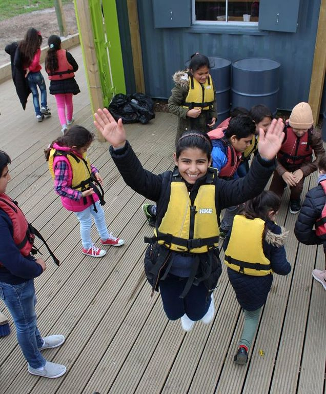 Smiling girl, jumping for joy, in lifejacket